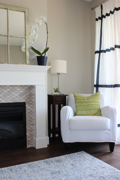 Green pillow from West Elm; chair slip cover from Fabricana; Ikea lamp; Fish scale travertine marble fire place surround from VanCity Tile; tile installation by GL Installations; vintage mirror