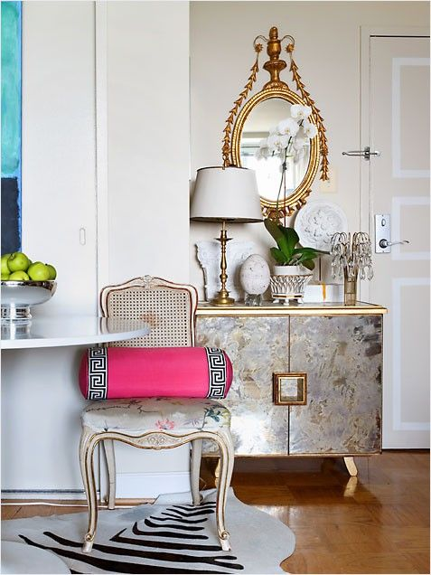 The antiqued glass of this console gives the appearance of a silver metal which contrasts the golden trim.