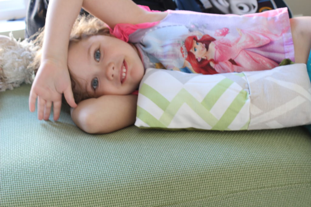 "Sofia with her finished project: a ""great big pillow"". All sewing a la Sofia with some pinning help from mommy."